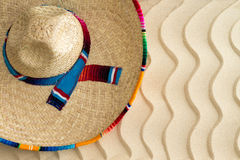 Straw sombrero on golden wavy beach sand. View from above of a Mexican straw sombrero with a colorful decorative ribbon lying on golden wavy beach sand with a Stock Image