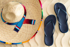 Straw sombrero and sandals on beach sand. Straw sombrero or sunhat with a colorful striped ribbon and slip-slops or sandals on golden tropical beach sand with a Royalty Free Stock Photos