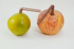 Straw stab in red apple and orange Royalty Free Stock Photography