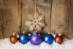Straw star and christmas balls Stock Photography