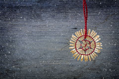 Straw star hanging in the snow against a wooden background as Ch Stock Images