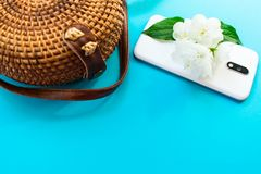 Straw stylish modern women`s summer bag and phone and  jasmine flower on a blue background. Summer vacation concept royalty free stock photo