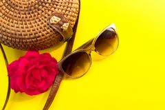 Straw stylish  women`s summer bag and sunglasses and a red rose flower on a yellow background. Summer vacation concept. Straw stylish modern women`s summer bag stock images