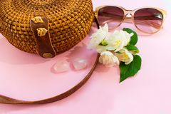 Straw stylish modern women`s  bag and sunglasses and white jasmine flower on a pink background. Summer vacation concept royalty free stock photo