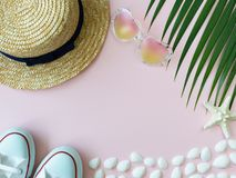 Straw summer hat, starfish, shells, heart-shape sunglasses, white sneakers and palm leaf royalty free stock photos