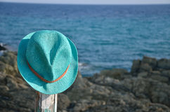 Straw summer hat on wooden pillar and sea Royalty Free Stock Photos