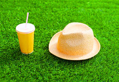 Straw summer hat with yellow cup of juice on a green textured grass. Background stock image