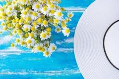 Straw Sun Hat Bouquet av nytt valda kamomillblommor på den blått red ut tabellen för plankaträträdgård Vårsommarbygd fotografering för bildbyråer