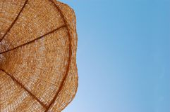 Straw sun umbrella against sunny sky Royalty Free Stock Photo