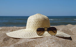 Straw and sunglasses on the beach Stock Photo