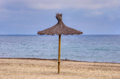 Straw sunshade on sandy beach. Royalty Free Stock Photography