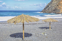 Straw sunshades at a pebbly beach. Lonesome pebbly beach with straw sunshades, Playa Hermigua, La Gomera, canary islands, Spain, Europe Royalty Free Stock Image