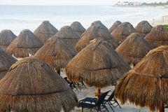 Straw Thatched Umbrellas on Tropical Beach. A tropical beach resort with straw thatched umbrellas over chairs Stock Images