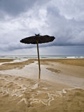 Straw Umbrella. Solitary straw umbrella located on the sand of a beach. Photo taken during a winter storm Royalty Free Stock Photo