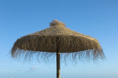 Straw umbrella. Tropical umbrella against blue sky Royalty Free Stock Image