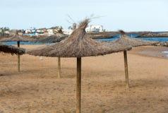 Straw umbrella on the beach Stock Photography