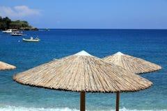 Straw umbrella on the beach Stock Photos