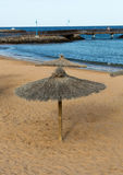 Straw umbrella on the beach Stock Images