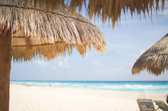 Straw umbrella on the beach. Straw palapa umbrellas on the white sand beach in Cancun, Mexico Royalty Free Stock Photo