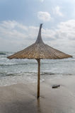 Straw umbrella on a beach with sand and water sea side. Stock Image