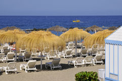 Straw umbrella and deckchairs at Tenerife Royalty Free Stock Image