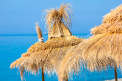 Straw umbrella hats. Yellow straw umbrella hats against blue sky-water background. Focus on the central hat Stock Photos