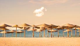 Straw umbrella rows on the sea shore Stock Photography