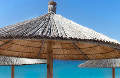 Straw Umbrella on sunny beach Royalty Free Stock Photos