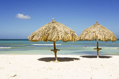 Straw umbrella on a tropical beach. On Aruba island Royalty Free Stock Photo