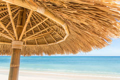 Straw umbrella on a tropical beach Royalty Free Stock Image