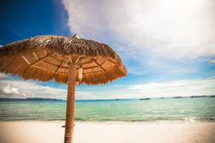 Straw umbrella on a tropical beach Royalty Free Stock Photography