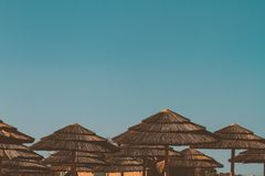 Straw Umbrellas à une plage dans le méditerranéen photographie stock libre de droits