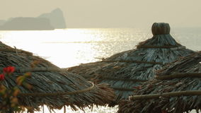 Straw umbrellas against the sea. At sunrise stock video footage