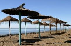 Straw umbrellas on beach. Straw umbrellas or parasols on beach near Gibraltar in Spain stock photography