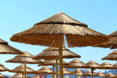 Straw umbrellas on the beach Stock Photography