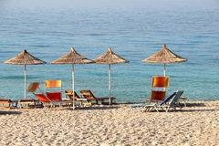 Straw umbrellas on the beach Stock Images