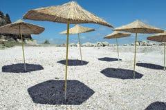 Straw umbrellas on the beach. Four Straw umbrellas on the beach on blue sky background Stock Image