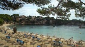 Straw umbrellas on the beach in Porto Cristo on Mallorca, Spain. PORTO CHRISTO, MAYORKA - SEPTEMBER 6, 2017: Straw umbrellas on the beach on Mallorca, Balearic stock footage