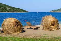 Straw umbrellas on the beach Royalty Free Stock Images