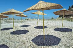 Straw umbrellas on the beach. Straw umbrellas from unstroke on the beach on blue sky background Royalty Free Stock Images