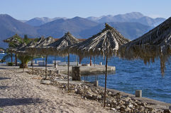 Straw umbrellas and blue sea. Adriatic coast of Montenegro in the winter. Blue sea and mountains in front resemble us about summer times Stock Photography