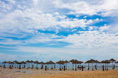Straw umbrellas on the clean sandy beach after the rain. Is Lisbon Portugal royalty free stock photo