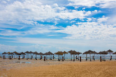 Straw umbrellas on the clean sandy beach after the rain. Is Lisbon Portugal stock photo