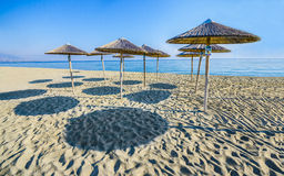 Straw umbrellas on empty beach Royalty Free Stock Photo