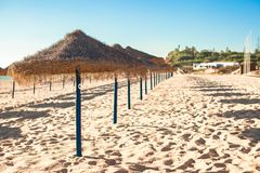 Straw umbrellas at empty tropical beach on the Royalty Free Stock Photos