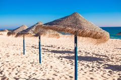 Straw umbrellas at empty tropical beach on the Royalty Free Stock Image