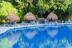 Straw umbrellas and lounge chairs around outdoor swimming pool. Riviera Maya, Cancun, Mexico Stock Photo