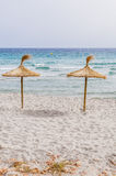 Straw umbrellas on sand beach. Royalty Free Stock Photography