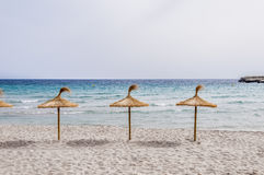 Straw umbrellas on sand beach. Straw umbrellas on sand beach and clear sky royalty free stock photography