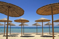 Straw umbrellas by the sea Royalty Free Stock Photo